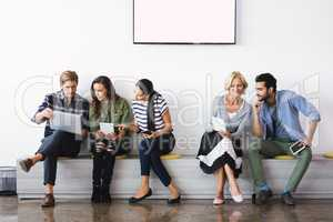 Business people using technologies while sitting against wall
