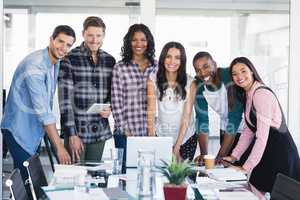 Portrait of smiling creative business team standing around desk