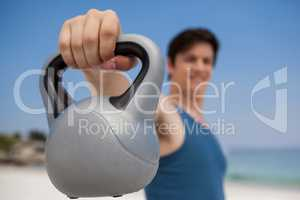 Low angle view of man holding kettlebell at beach
