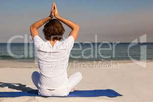 Man performing yoga at beach on sunny day