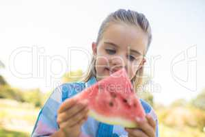 Smiling girl looking at watermelon slice in the park