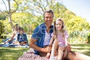 Daughter sitting on fathers lap in park