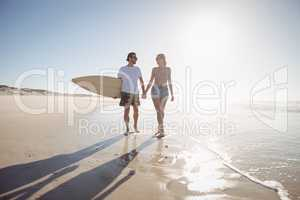 Young couple holding hands at beach during sunny day