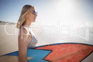 Woman holding surfboard at beach