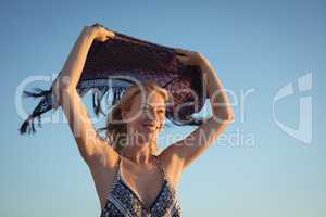 Happy woman holding scarf against clear sky