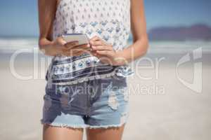 Mid section of woman using mobile phone at beach