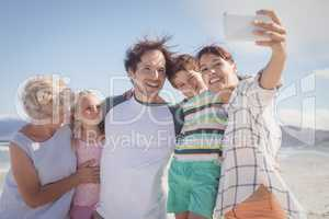 Happy multi-generation family taking selfie at beach