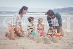 Happy siblings with parents making sand castle
