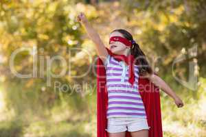 little girl trying to fly while wearing superhero costume