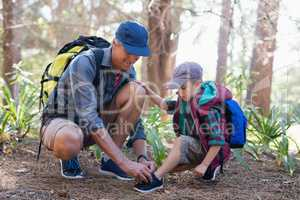Father tying shoelace for son in forest