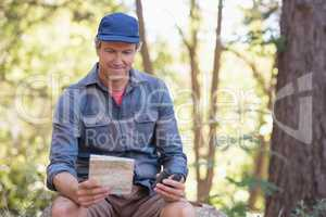 Happy hiker reading map while sitting on rock