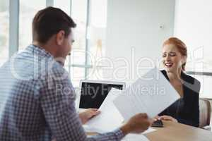 Executive discussing over document at desk