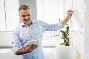 Attentive executive using digital tablet while writing on whiteboard