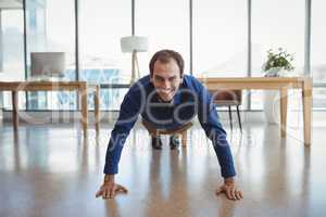 Portrait of smiling executive doing push-ups