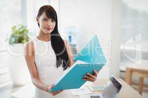 Portrait of beautiful executive holding file at desk