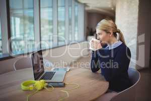 Female executive having cup of coffee at desk