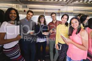 Portrait of business people standing in elevator