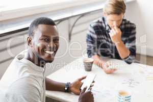 Portrait of smiling businessman sitting with colleague