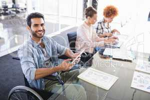 High angle portrait of smiling businessman using digital tablet while sitting on wheelchair