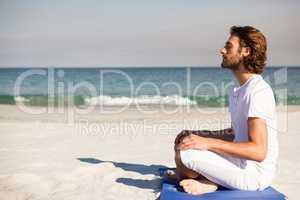Man performing yoga at beach
