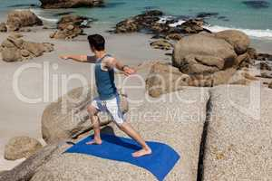 Man performing yoga on rock