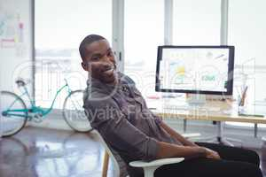 Smiling businessman sitting in brightly lit office