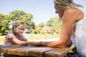 Mother and daughter holding hands on picnic table