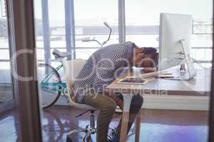 Tired businessman napping on desk seen through glass