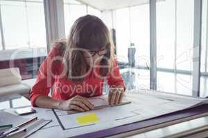 Focused female interior designer working in office