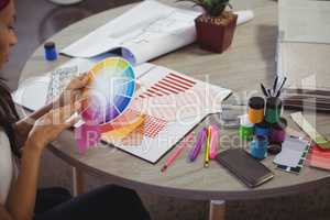 Businesswoman holding colour swatch at office desk