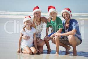 Portrait of smiling family wearing Santa hat at beach