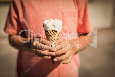 Mid section of smiling boy holding ice cream at beach