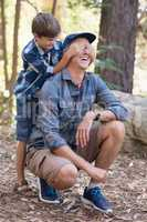 Playful boy covering fathers eyes while hiking
