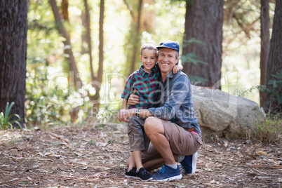 Full length portrait of smiling father and son in forest