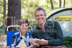 Smiling father and son using mobile phone by tent in forest