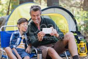 Father and son taking picture by tent in forest