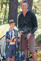 Smiling father and son holding hiking poles in forest