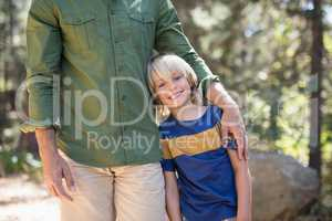 Smiling boy standing with father on sunny day in forest