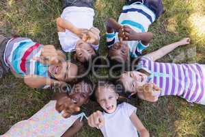 Portrait of smiling friends pointing up while lying on grassy field