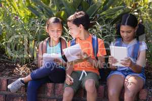 Girl using digital tablet while friends discussing over book