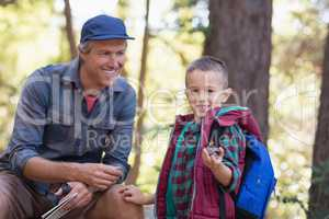 Happy man looking at boy holding pine cone in forest