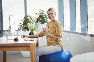 Portrait of smiling executive sitting on fitness ball while working at desk