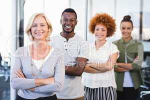 Portrait of smiling business people with arms crossed standing in row