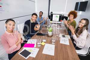 Portrait of colleagues clapping after presentation at creative office