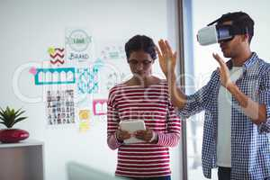 Female colleague assisting man while using virtual reality headset