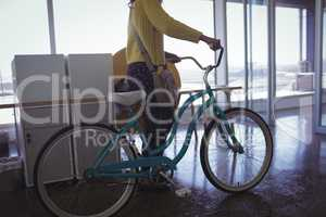 Businesswoman with bicycle creative office