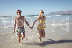 Happy young couple holding hands while running at beach