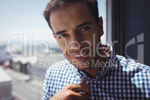 Portrait of young businessman by window in office