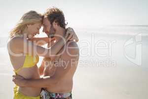 Side view of young couple embracing at beach