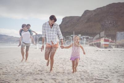 Happy family running on sand